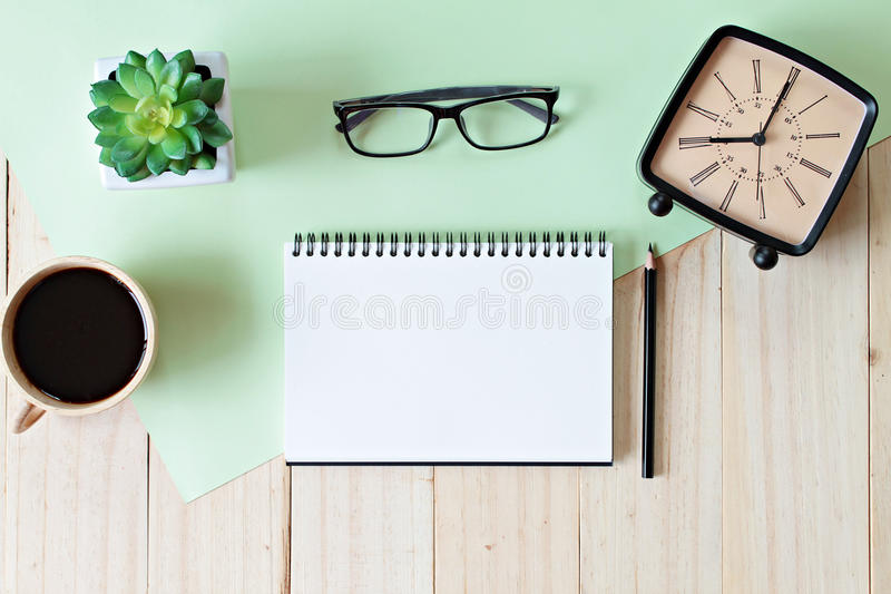 Top view image of open notebook with blank pages, retro alarm clock and coffee cup on wooden background, ready for adding or mock. Still life, business, office royalty free stock images