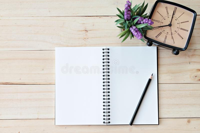 Top view image of open notebook with blank pages and retro alarm clock on wooden background, ready for adding or mock up. Still life, business, office supplies royalty free stock photography