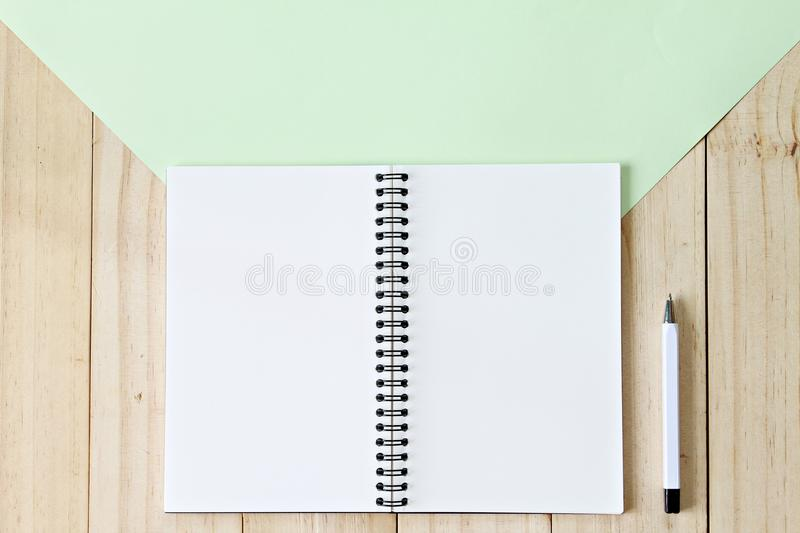 Top view image of open notebook with blank pages on wooden background, ready for adding or mock up. Still life, business, office supplies or education concept stock photography