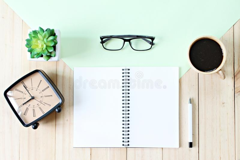 Top view image of open notebook paper with blank pages, accessories and coffee cup on wooden background, ready for adding or mock. Still life, business, office stock images