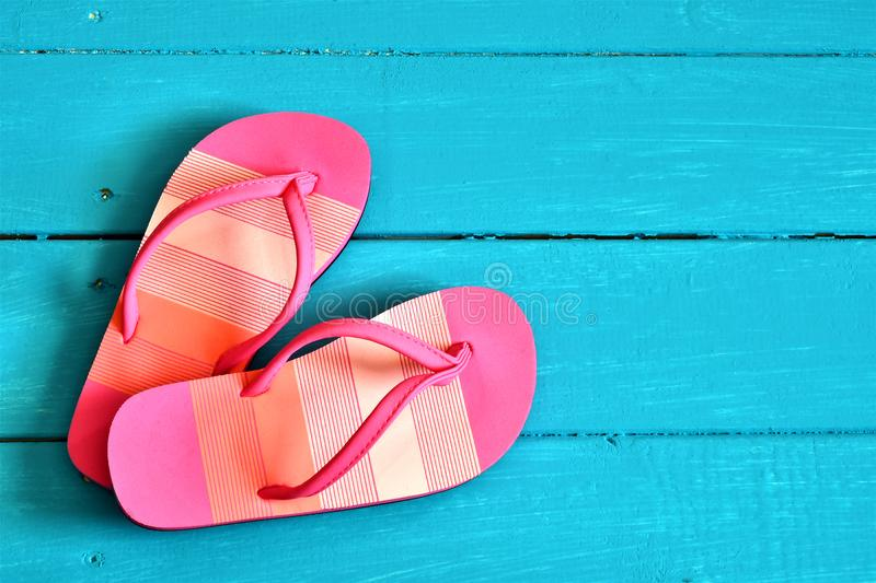Pink Ladies Flip-Flop Sandals. A top view image of a pair of pink ladies flip-flop sandals on a bright tropical blue background royalty free stock photo