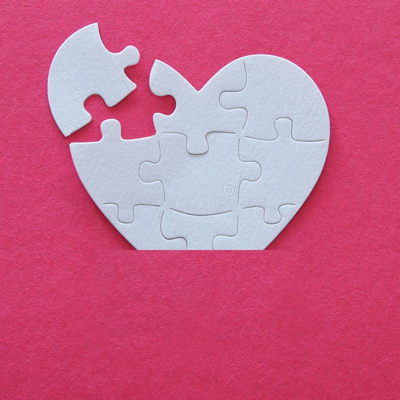 Top view image of paper white heart puzzle with missing piece over pink background. Health care, donate, world heart day and world stock photography
