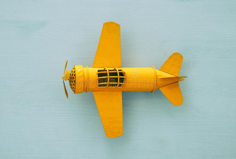 Top view image of retro yellow metal toy airplane over blue background. stock photo