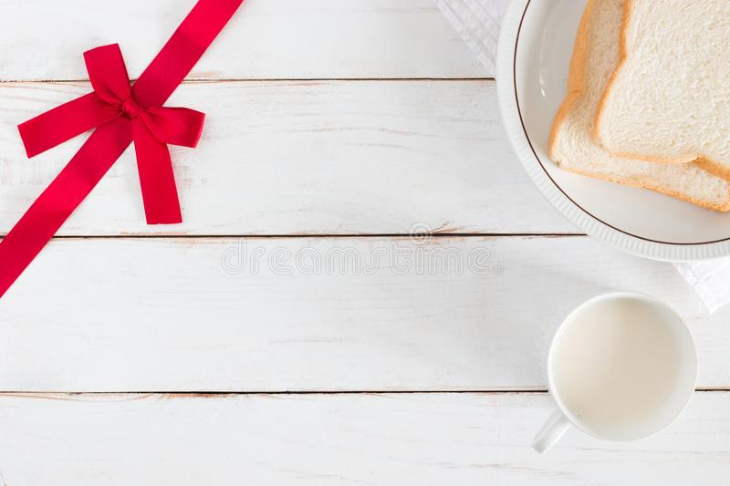 Top view image of Sliced bread on dish with hot milk in white cup and Corner have ribbon on white wood table background stock images