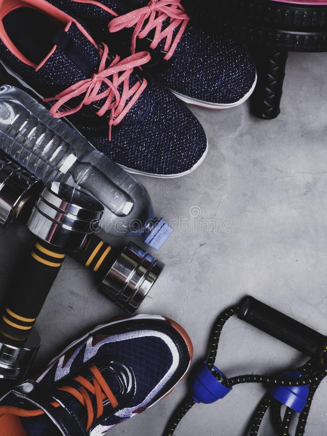 Top view image of sport shoes, dumbbells, press roll, water, expander. Fitness or workout equipment. Weight loss and sports stock photography