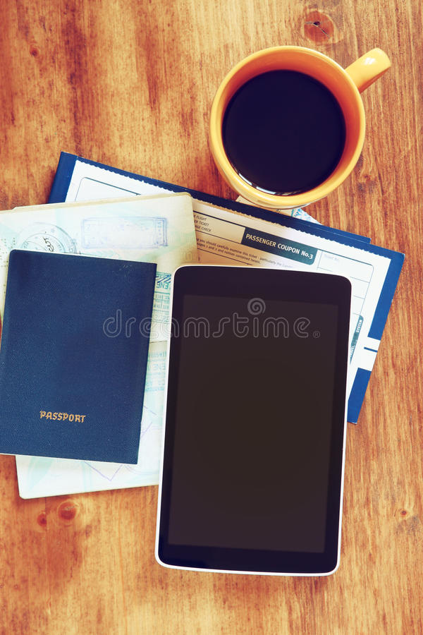 Top view image of tablet with empty screen, old camera passport and flight boarding pass. stock photos