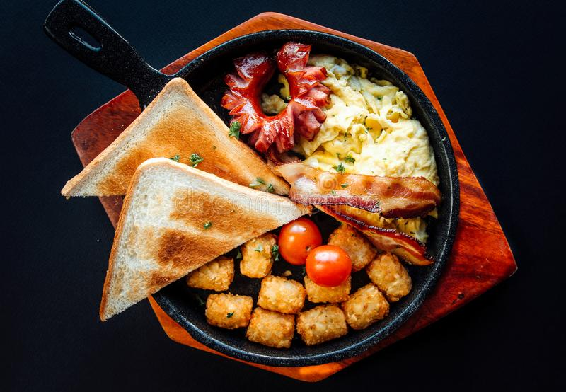 Top view image of western brunch menu on pan and wooden plate. American style breakfast served with toast, hash brown, sausages, stock image
