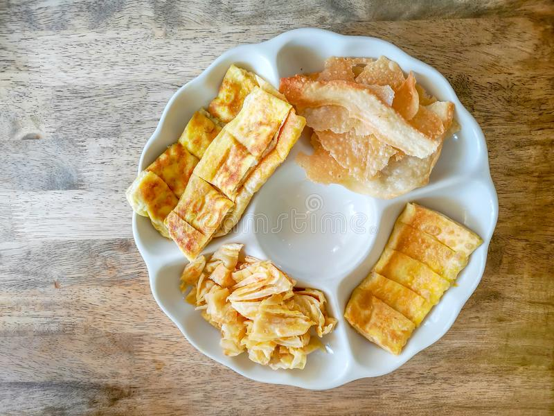 Top view image, a white plate of yellow brown crunchy and crispy roti or bolloon bread fired Indian style snack, on wooden table royalty free stock photography