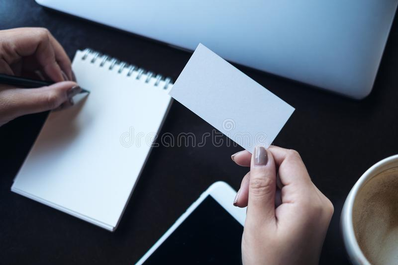 A womans hands holding empty white business card and writing on download a womans hands holding empty white business card and writing on blank notebook colourmoves