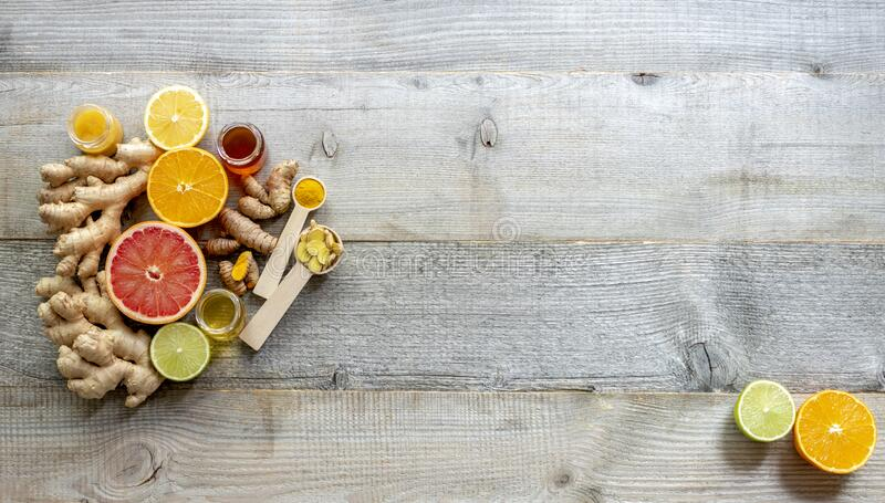 Top view on the immune system booster frame - ginger, turmeric, citruses, and honey. On the old wooden table, flat lay, copy space stock photography