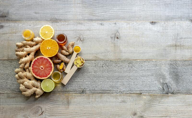 Top view on the immune system booster - ginger, turmeric, citruses, and honey on the old wooden board. Top view, copy space stock image