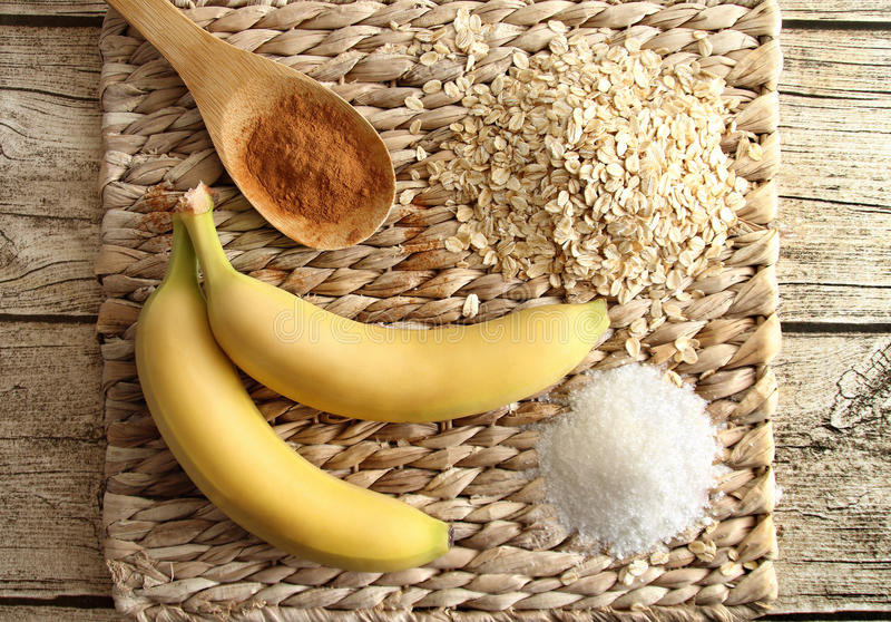 Top view of ingredients of diet cookies - banana, oatmeal, sugar and cinnamon on a stand made of rattan. stock photography