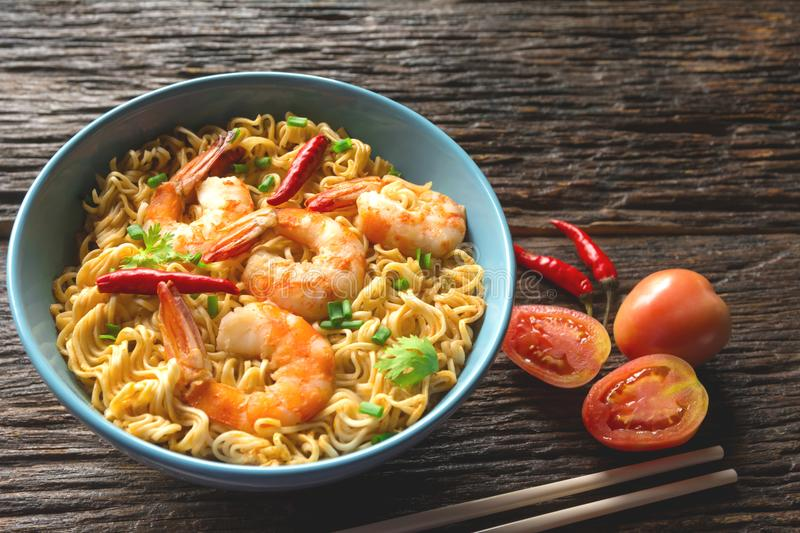 Top view of instant noodles with shrimp and chopsticks on wooden stock photo
