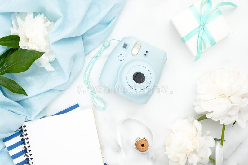 Top view instant photo camera, paper notepad, white peony flowers, blue scarf on marble background. Minimal flat lay style royalty free stock photos
