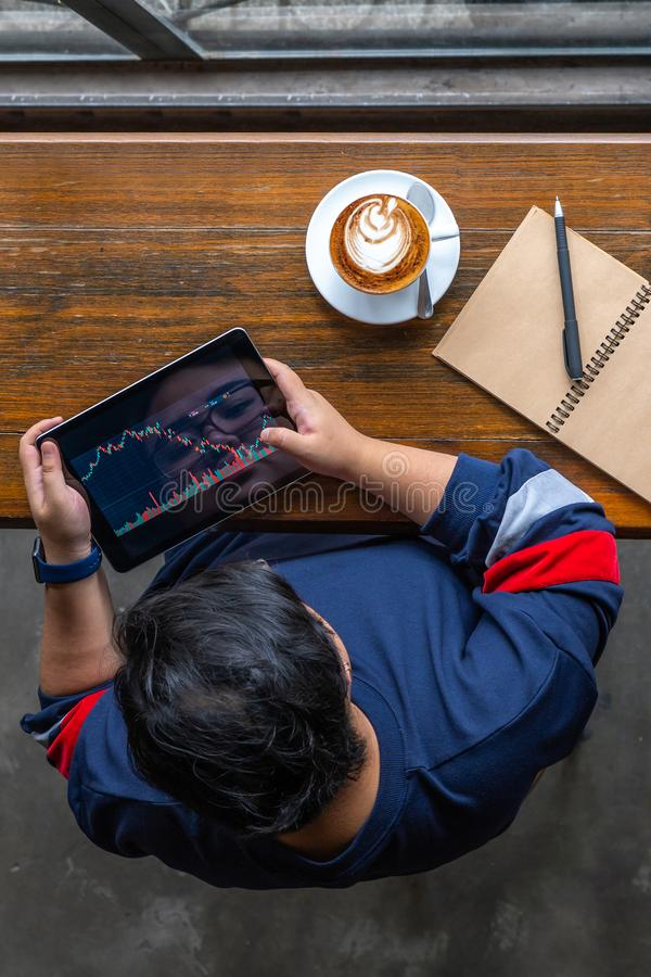 Vertical photo of investor watching stock trading graph on tablet. Top view of investor watching stock market trading graph on tablet royalty free stock images