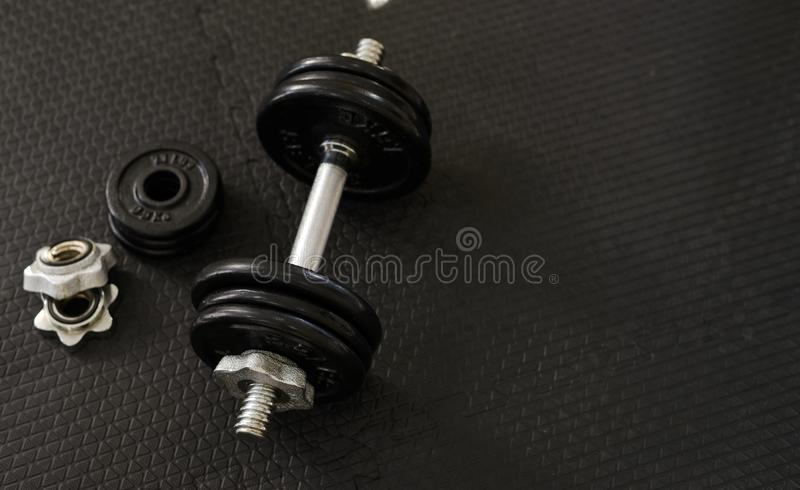Health care concept. Top view of Iron dumbbells or weights on black floor with copy space for text. Flat lay composition. Top view of Iron dumbbells or weights stock photos