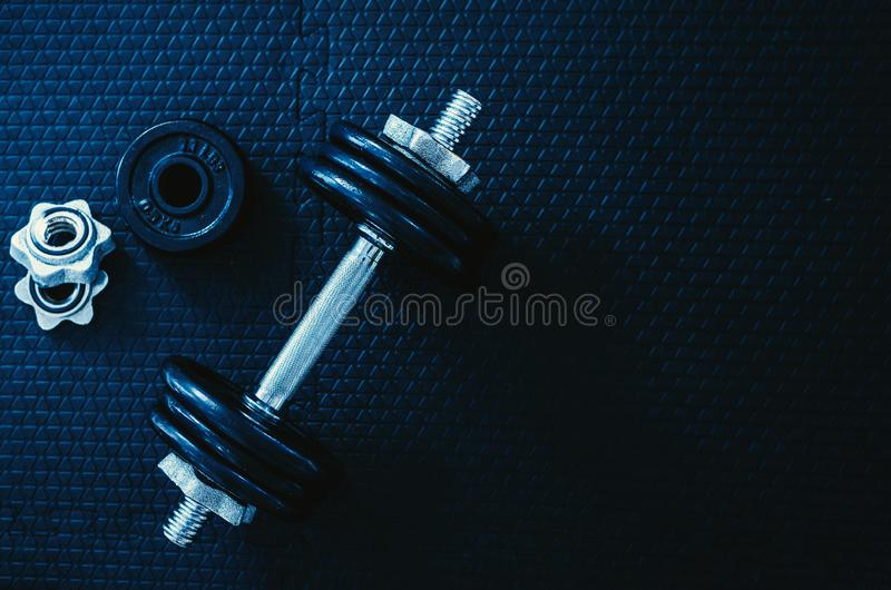 Health care concept. Top view of Iron dumbbells or weights on black floor with copy space for text. Flat lay composition. Top view of Iron dumbbells or weights royalty free stock photo