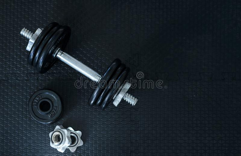 Health care concept. Top view of Iron dumbbells or weights on black floor with copy space for text. Flat lay composition. Top view of Iron dumbbells or weights stock images