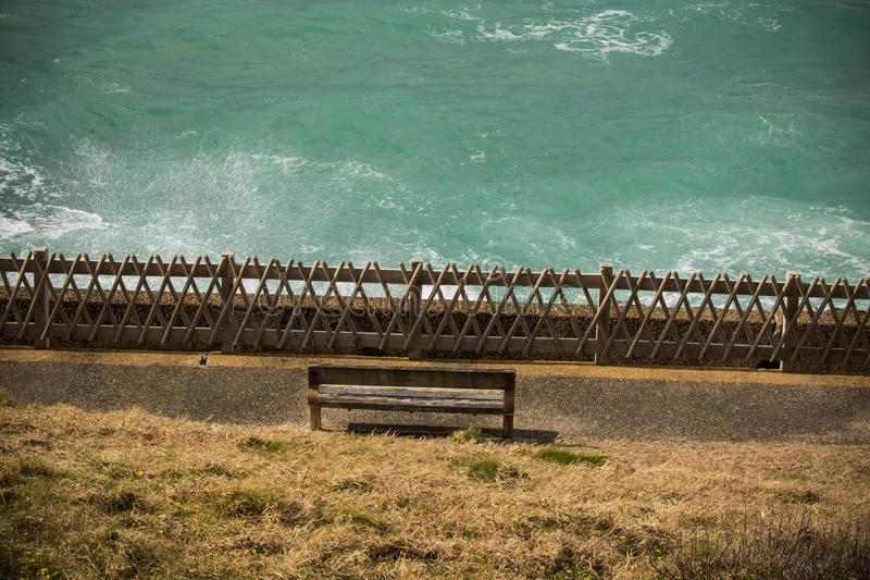Top view on isolated bench on the shore with breaking waves of atlantic ocean, bidart, france royalty free stock photo