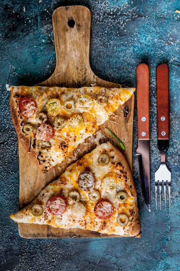 Top view italian pizza with tomatoes and mozzarella on a wooden cutting board. Vertical shot stock photography