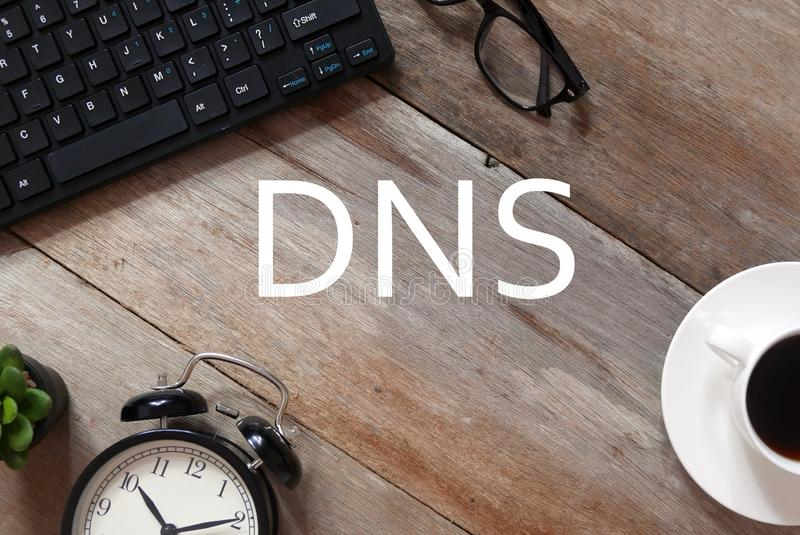 Top view of keyboard,sunglasses,a cup of coffee,clock and plant on wooden background written with DNS stock image