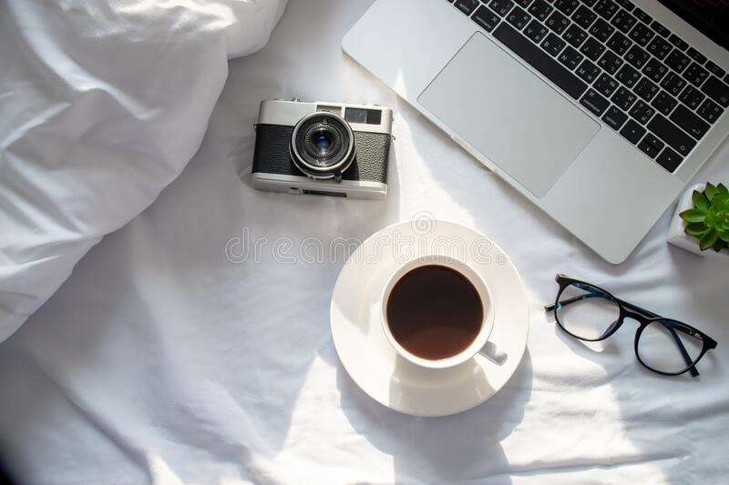 Top view, laptop computer, hot coffee, film camera and eyeglasses on the bed with morning sun.  royalty free stock photography