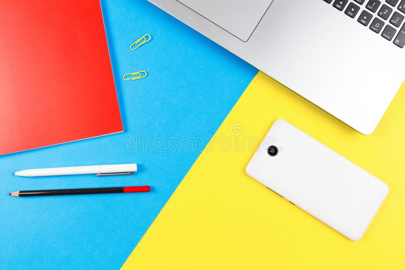 Top view of laptop computer, paper notebook, pencil and pen on blue and yellow color background royalty free stock image