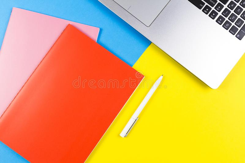 Top view of laptop computer, paper notebooks and white pen on blue and yellow color background stock image