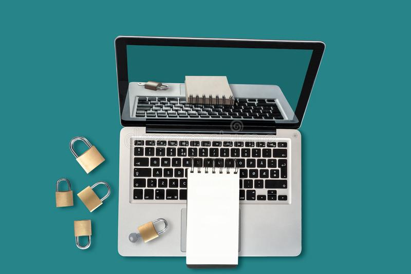 Top view of a laptop, padlocks and a blank notepad with copyspace, a security concept. Modern, vibrant photo illustrating the concept of cybersecurity, password stock image