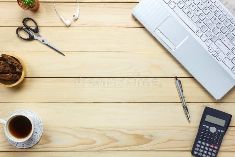 Top view laptop ,pen,black coffee,calculator,stationary,earphones,cookies on office desk background. stock image