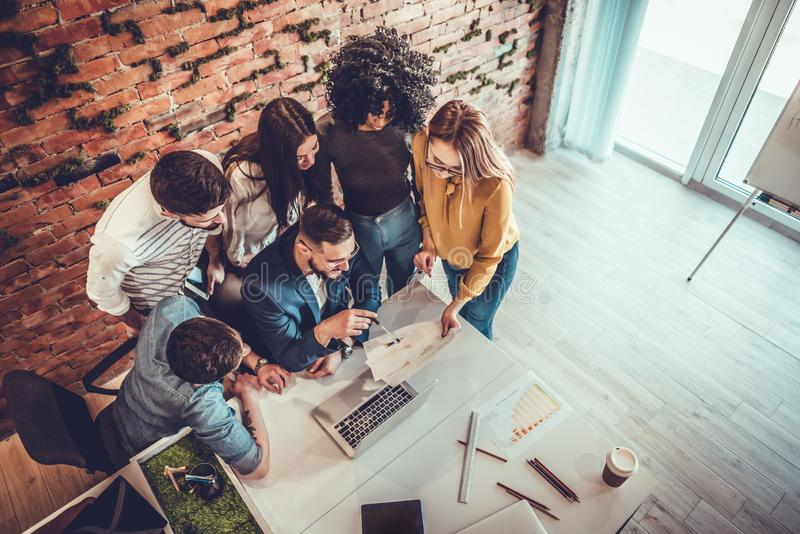 Top view of the large Desk behind which the office team of creative managers of different nationalities makes brainstorming. Group, business, work, person royalty free stock photo