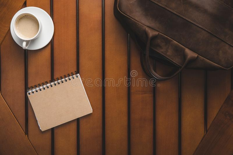 Top view of leather bag, notepad and cup of coffee. On wooden table royalty free stock image