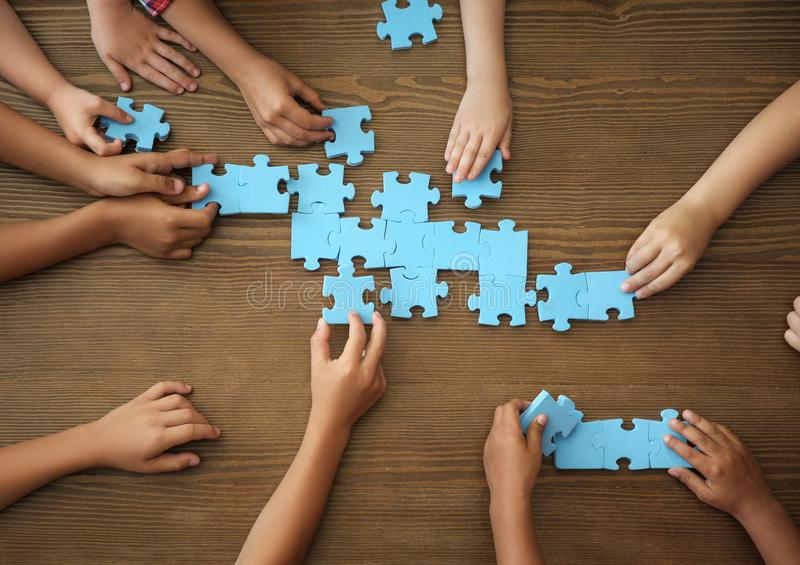 Top view of little children playing puzzle together at table, focus on hands stock photo