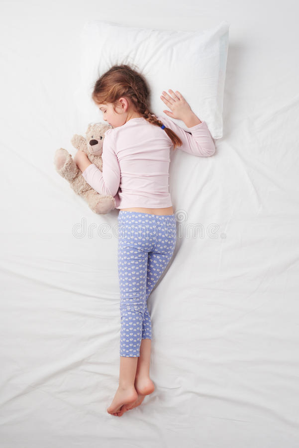 Top view of little cute girl sleeping with teddy stock photography