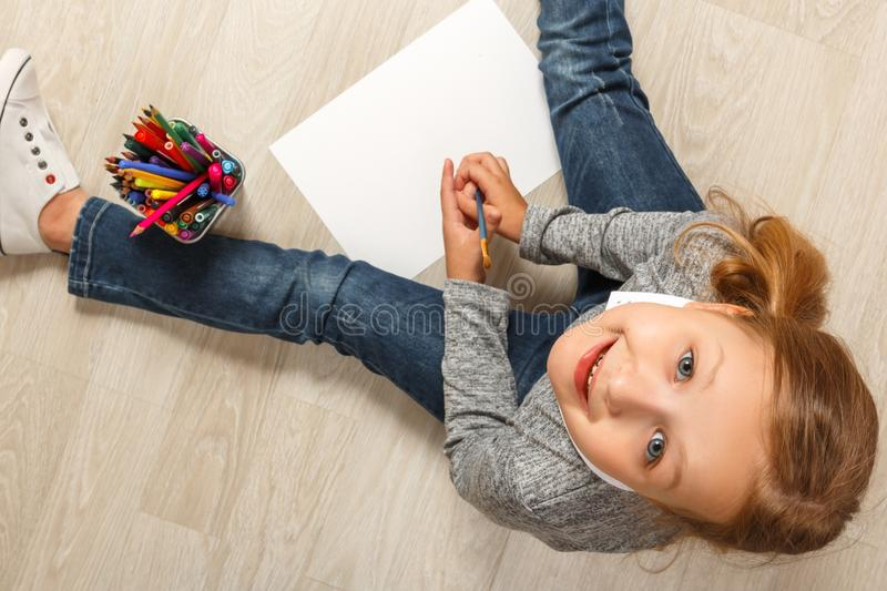 Top view of little girl painting, looking at camera and sitting on the floor in her room at home stock image