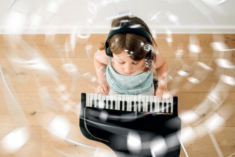 High angle view of a female child playing toy piano. Top view of a little girl playing piano with headphones at home - musical notes flying around stock photos
