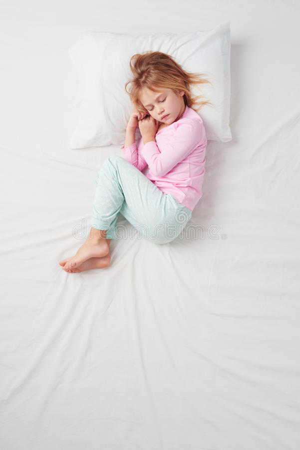 Top view of little girl sleeping in Foetus pose stock photography