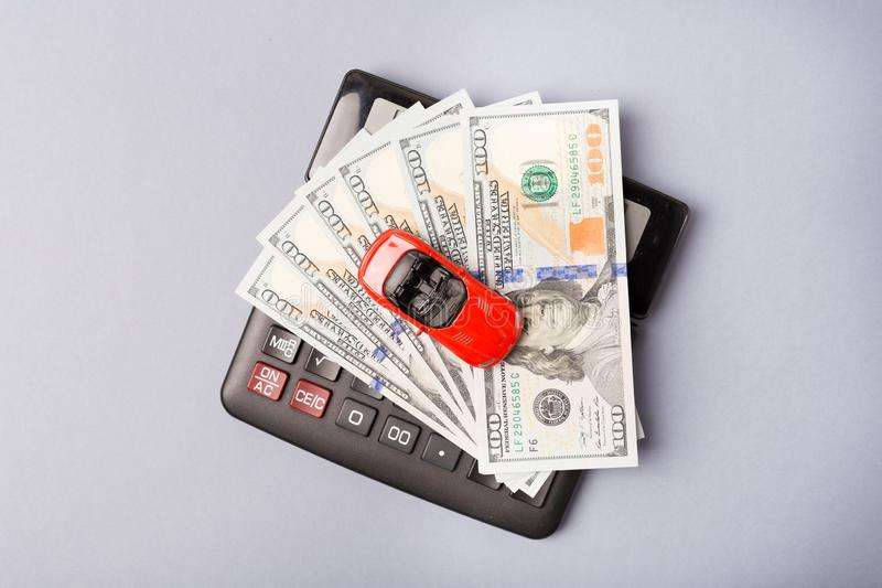 Top view. Little red car over calculator and pile of money dollars. Cost calculation expenses for loans costs and stock images