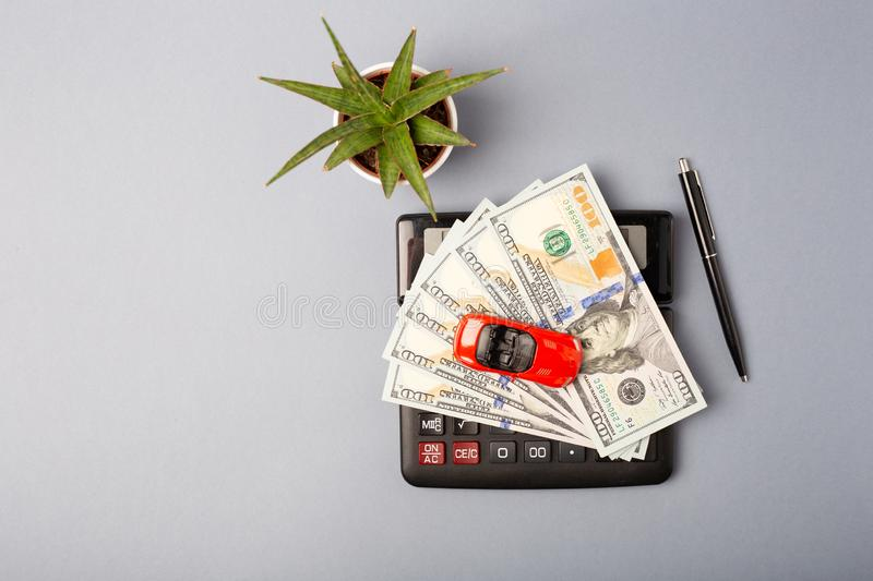 Top view. Little red car over calculator and pile of money dollars. Cost calculation expenses for loans costs and royalty free stock image