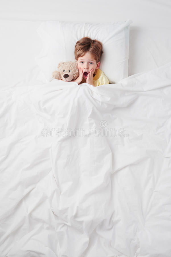 Top view of little scared by nightmares boy under royalty free stock image