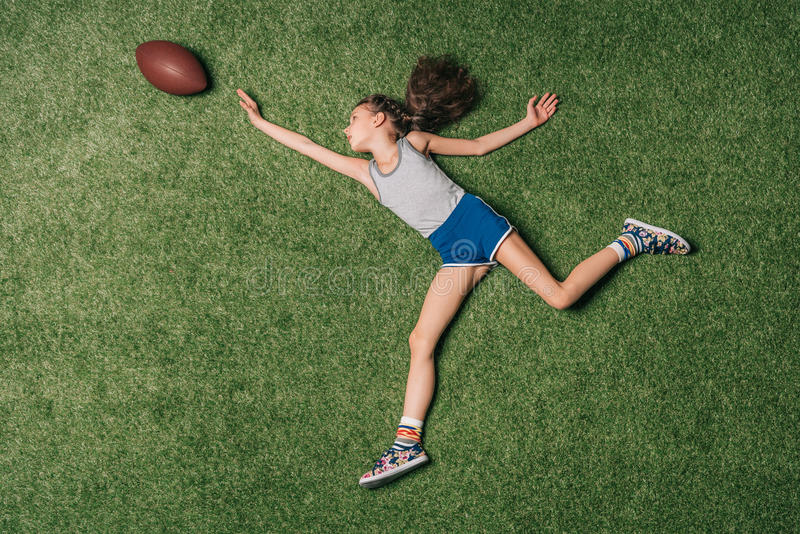 Top view of little sportive girl catching rugby ball on grass, royalty free stock images