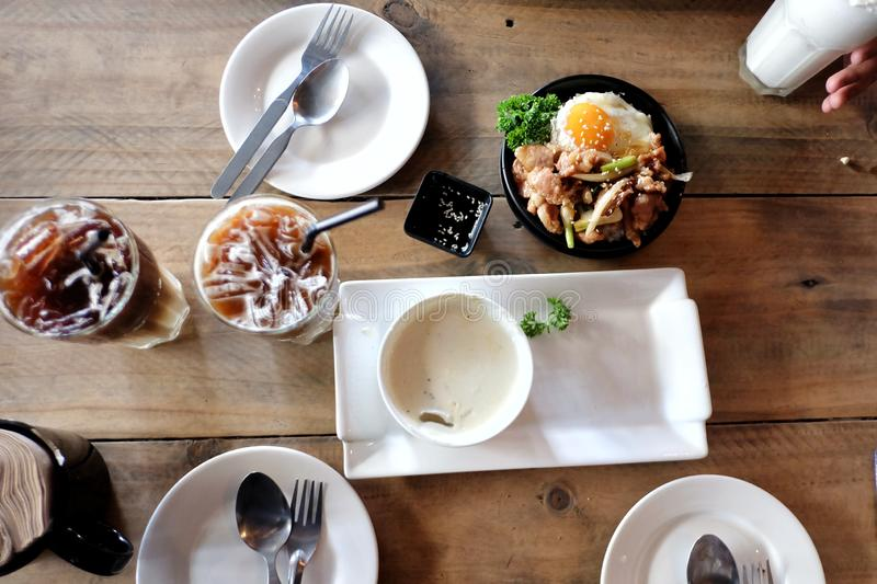 Top view a lot of meal on old wooden table with iced coffee, a cup of soup, a dish of Korean pork royalty free stock photo