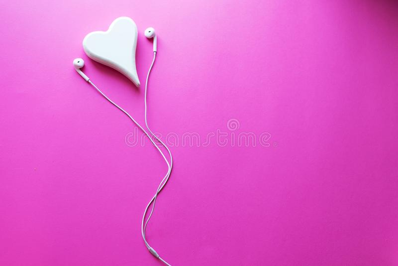 Top view Lovely Closeup of White Earphones on Pink Pastel plastic texture background. Pastel color concept, Minimal concept. royalty free stock photography