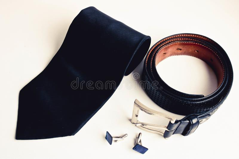 Top view of luxury men`s accessories. Black silk tie, black leather belt and cufflinks. stock photography