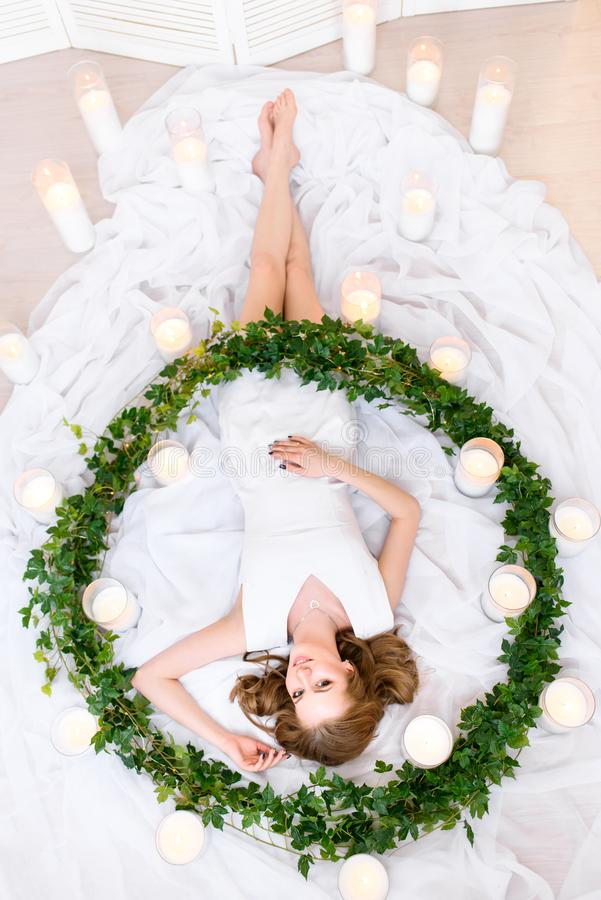 Top view on a lying girl in a white dress in a green wreath , slender figure and a charming smile on her face. Beautiful girl royalty free stock photo