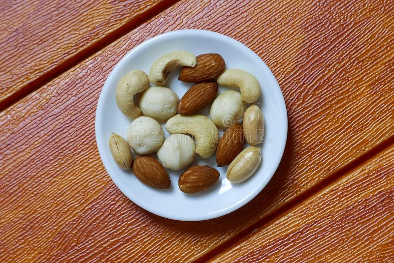 Top view of macadamia,cashew,almond and peanuts nuts in bowl on wooden background. stock image