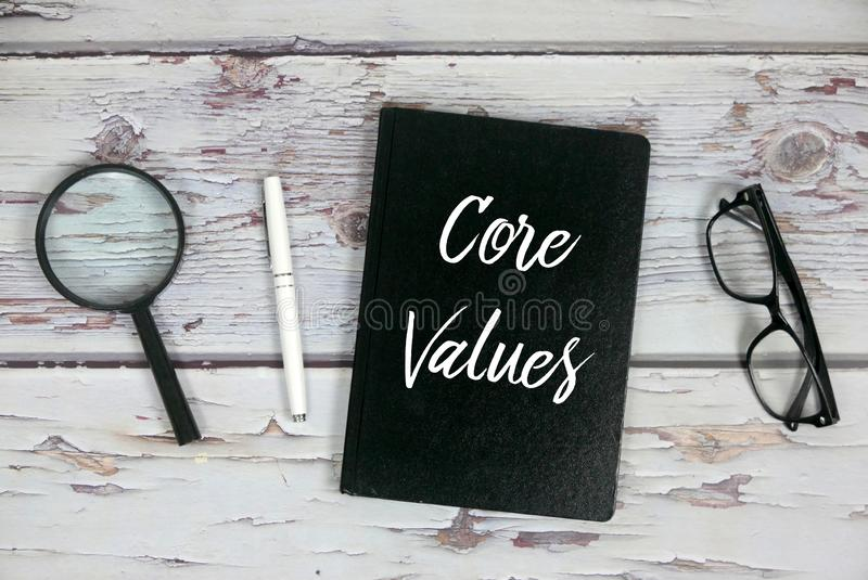 Top view of magnifying glass,pen,sunglasses, and notebook written with Core Values. Company, business, vision, mission, integrity, concept, culture, conduct stock photography