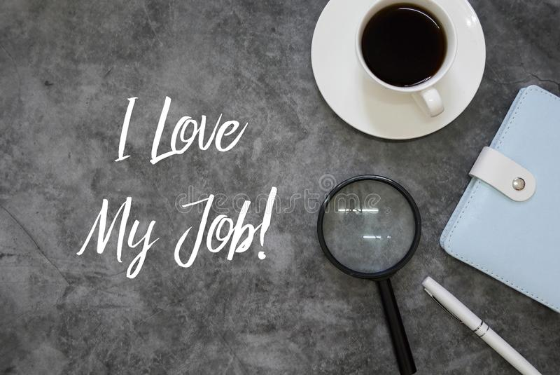 Top view of magnifying glasses,pen,notebook and coffee on grey grunge floor written with I Love My Job. Business positive happy message satisfaction office royalty free stock photos
