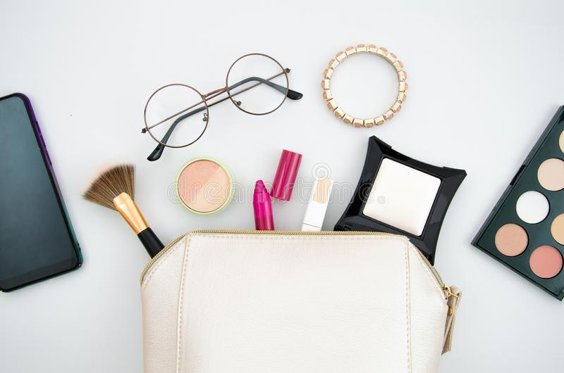 Top view make up bag with cosmetics and brushes, glasses and smartphone isolated on white. Beauty concept.  royalty free stock image