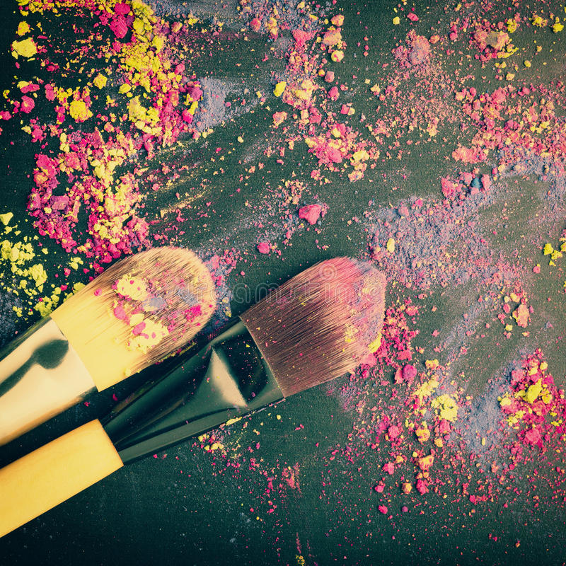 Top view of make-up brushes on colorful eyeshadow. On black texture royalty free stock images